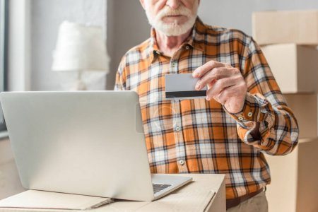 partial view of senior man making online purchase with credit card and laptop