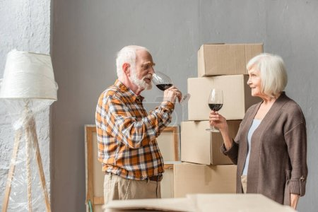 happy senior couple celebrating moving into new house with glasses of wine