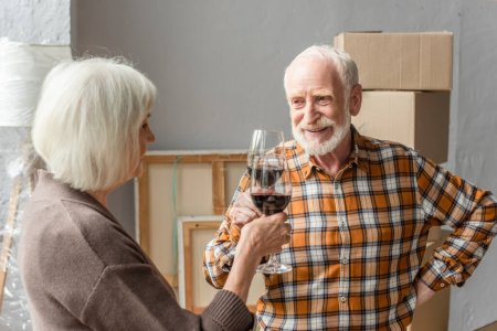 smiling senior couple clinking glasses of wine, moving concept