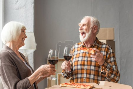 laughing senior man holding piece of pizza and looking at wife while holding glasses of wine