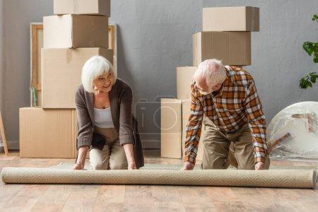 senior couple rolling carpet on knees with boxes, frames and plant on background