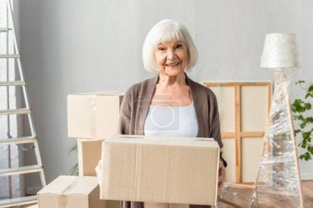 cheerful senior woman holding cardboard box and looking at camera, moving concept