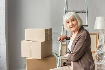 senior woman sitting on ladder with cardboard boxes on background, moving concept