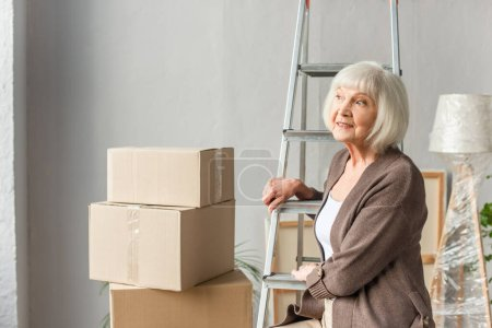 Photo for Smiling senior woman sitting on ladder and looking away with cardboard boxes on background, moving concept - Royalty Free Image