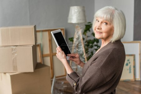 senior woman holding digital tablet with blank screen and looking back with cardboard boxes on background, moving concept