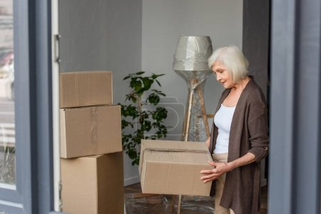 Photo for Cheerful senior woman holding cardboard box, moving concept - Royalty Free Image