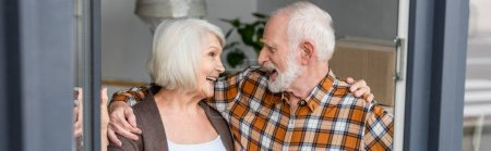 panoramic shot of laughing senior couple looking at each other and moving to new house