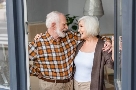 laughing senior couple looking and embracing each other in new house