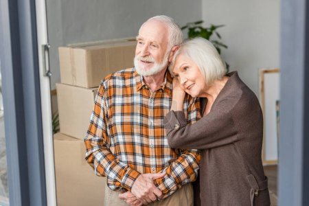 Photo for Cheerful senior woman leaning on husband shoulder in new house - Royalty Free Image