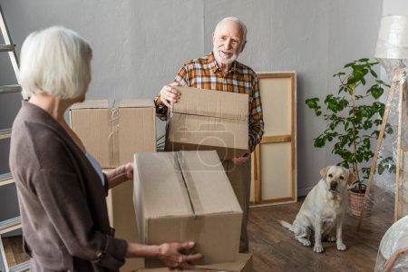 Seniorenpaar hält Pappkartons in neuem Haus, während Hund in der Nähe sitzt