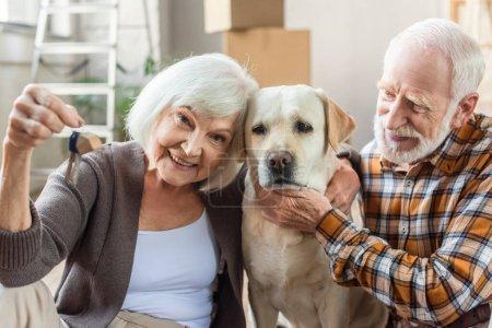 Photo pour Senior homme caressant chien tandis que femme tenant des clés, concept mobile - image libre de droit