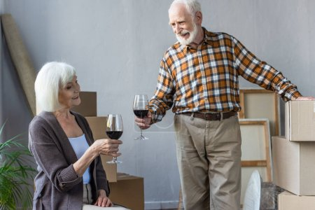 senior couple celebrating moving to new house with glasses of wine