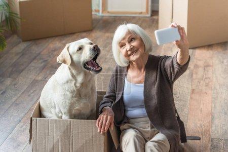 senior woman taking selfie with dog sitting in box