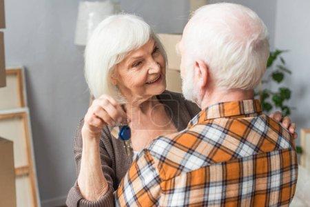 senior woman holding keys and hugging husband, moving concept