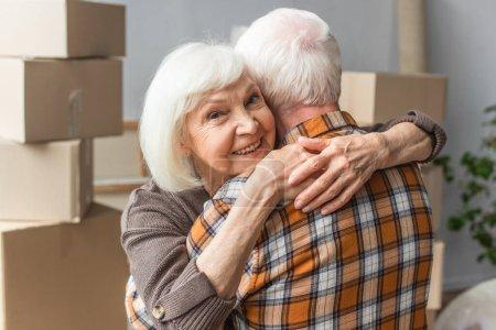 Seniorin umarmt Ehemann in neuem Haus, bewegendes Konzept