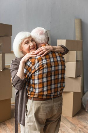 senior woman with closed eyes hugging husband in new house, moving concept