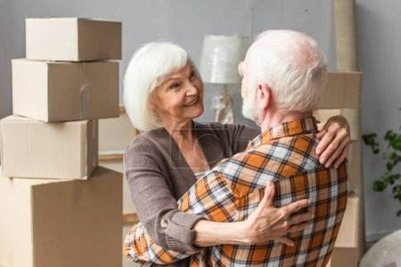 happy senior couple hugging and looking at each other in new house