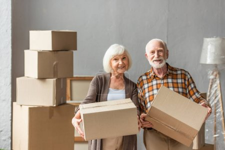 senior couple holding cardboard boxes and looking at camera in new house, moving concept