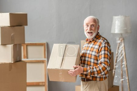 Photo for Surprised senior man holding cardboard box in new house, moving concept - Royalty Free Image