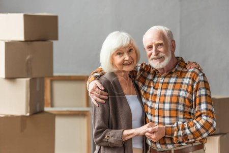 senior couple embracing and holding hands in new house, moving concept