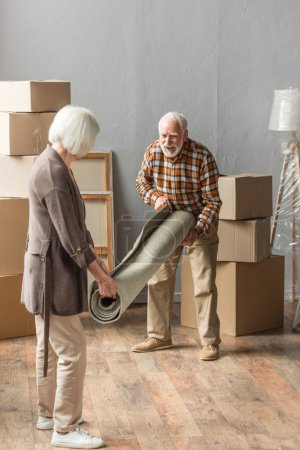 full length view of senior couple rolling carpet in new house, moving concept
