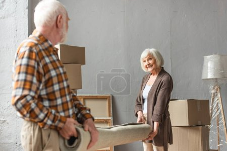 senior couple rolling carpet in new house, moving concept