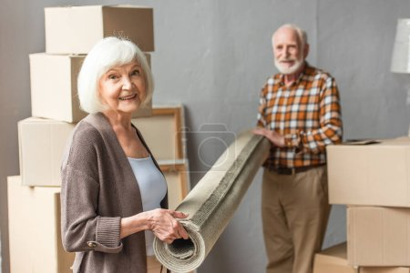 smiling senior couple rolling carpet in new house, moving concept
