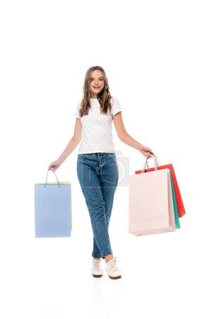 heureux jeune femme tenant sacs à provisions et regardant caméra isolé sur blanc