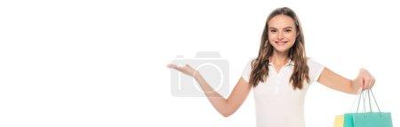 Photo pour Concept panoramique de femme heureuse pointant avec la main et tenant des sacs à provisions isolés sur blanc - image libre de droit
