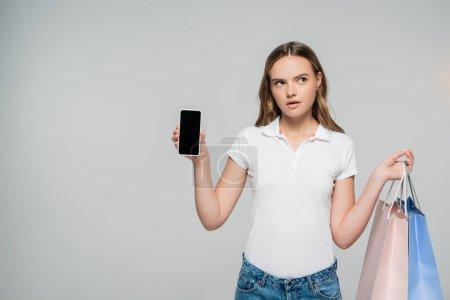 Photo pour Femme coûteuse tenant smartphone avec écran vierge et sacs à provisions isolés sur gris - image libre de droit