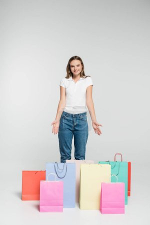 young joyful woman standing and pointing with hands at shopping bags on grey, black friday concept