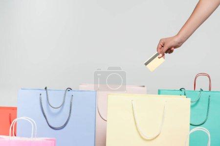 Photo pour Vue recadrée de la femme tenant une carte de crédit près des sacs à provisions isolés sur gris, concept du vendredi noir - image libre de droit
