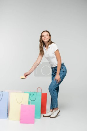 Photo for Joyful woman holding credit card near shopping bags on grey, black friday concept - Royalty Free Image