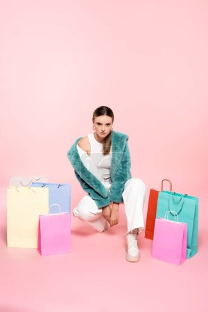 Photo for Young customer in faux fur jacket sitting near shopping bags on pink, black friday concept - Royalty Free Image