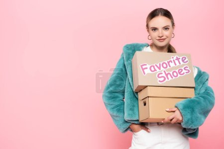 Photo for Pleased woman in sunglasses holding boxes with favorite shoes lettering on pink, black friday concept - Royalty Free Image