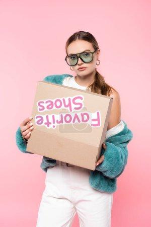 junge Frau in Sonnenbrille mit Box mit Lieblingsschuhen Schriftzug auf rosa, schwarzem Freitag Konzept