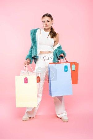 Photo pour Élégant jeune client tenant des sacs à provisions avec des étiquettes de vente sur rose, concept vendredi noir - image libre de droit