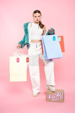 Photo for Young customer holding shopping bags with sale tags and standing near box with favorite shoes lettering on pink, black friday concept - Royalty Free Image