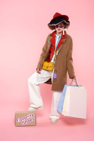 woman in sunglasses and hats with sale tags holding shopping bags and standing near box with favorite shoes lettering on pink
