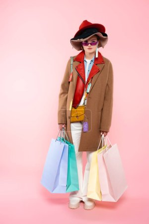 woman in sunglasses and hats with sale tags holding shopping bags and standing on pink