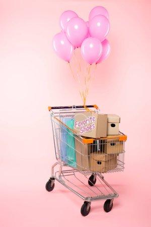 Warenkorb mit Einkaufstaschen und Kartons in der Nähe von Luftballons auf rosa, Black Friday Konzept