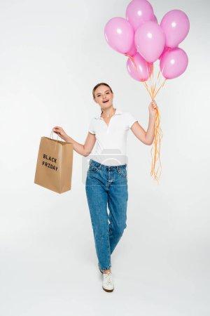 Photo pour Joyeuse femme tenant sac à provisions avec lettrage noir vendredi et ballons roses sur blanc - image libre de droit