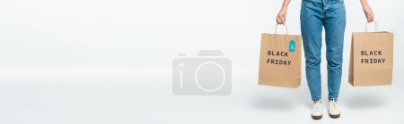 customer holding shopping bags with sale tag and black friday lettering isolated on white, panoramic shot