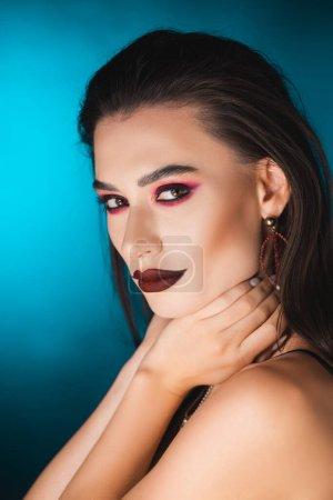 Photo pour Jeune femme avec un maquillage sombre regardant la caméra et touchant le cou sur bleu - image libre de droit
