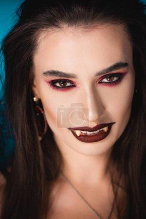 Photo pour Vampire avec maquillage noir et dents blanches effrayantes regardant la caméra - image libre de droit