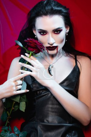 Photo pour Jeune femme pâle avec du sang sur le visage tenant rose sur rouge - image libre de droit