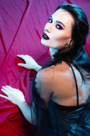 Photo pour Pâle et jeune femme avec maquillage noir regardant la caméra sur rouge - image libre de droit