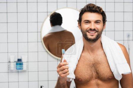 Hombre sin camisa sonriente con toalla alrededor del cuello sosteniendo el cepillo de dientes en el baño