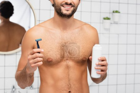 Photo pour Vue recadrée de sourire homme torse nu tenant rasoir et mousse à raser dans la salle de bain - image libre de droit
