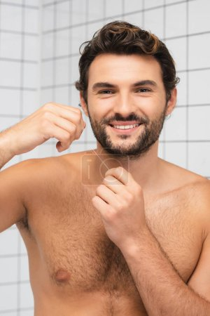 Shirtless man smiling at camera while holding dental floss in bathroom